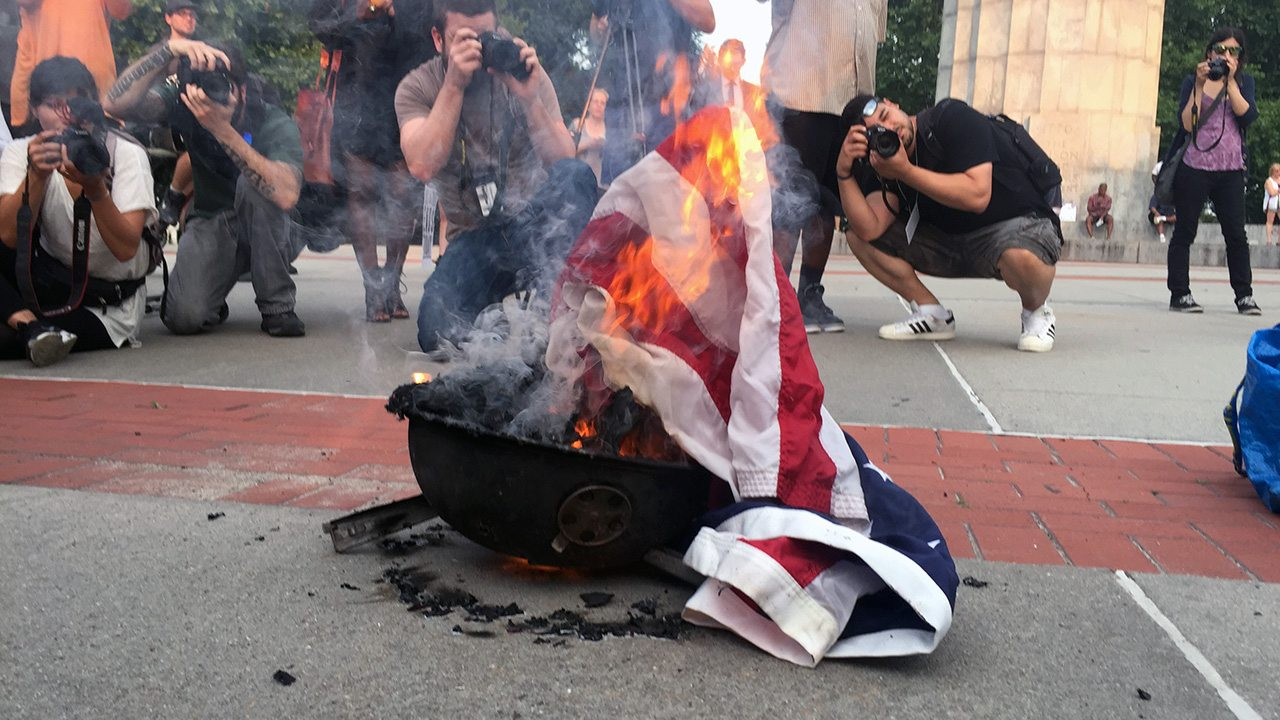 the burning of the american flag by prostesters According to reports, protesters cursed at student trump supporters and burned the american flag in rejection of trump's victory this is a representation of america we are going down in flames a female student yelled as she began to light an american flag on fire.