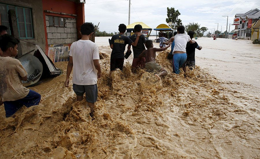 Residents wade along a flooded road amidst a strong current in Sta Rosa, Nueva Ecija in northern Philippines October 19, 2015, after it was hit by Typhoon Koppu. Powerful typhoon Koppu ploughed into the northeastern Philippines before dawn on Sunday destroying homes and displacing 10,000 people and whipping up coastal surges four meters (12 feet) high, disaster agency officials said. There were no reports of casualties after the category four typhoon, with central destructive winds of 175 kph (109 mph), making landfall near the town of Casiguran in the Aurora province. REUTERS/Erik De Castro - RTS514T