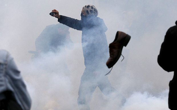 A shoe flies towards a demonstrator filming as protestors clash with riot police Photo: FRANCOIS GUILLOT/AFP