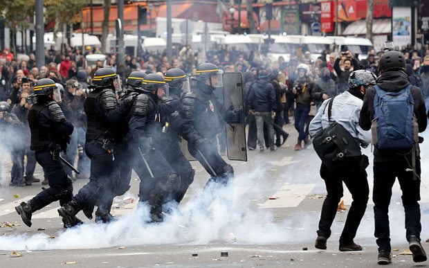Riot police move in in formation as tear gas is deployed in Paris Photo: FRANCOIS GUILLOT/AFP