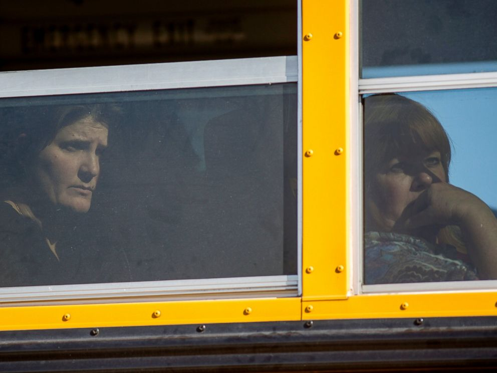 Employees and other people are evacuated by bus from the site of a mass shooting at the Inland Regional Center Dec. 2, 2015 in San Bernardino, Calif