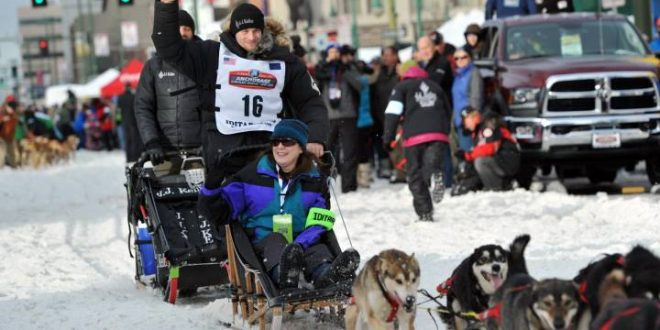 Defending Iditarod Trail Sled Dog Race champion Dallas Seavey (16) waves to the crowd as she begins the ceremonial start of the 1,000-mile race in Anchorage, Alaska, Saturday, March 5, 2016.