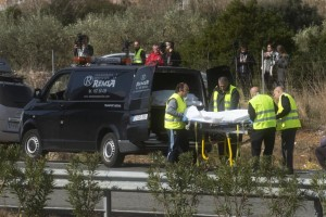Undertaker workers carry the body of a person killed during a bus accident on the AP7 highway that links Spain with France along the Mediterranean coast near Freginals halfway between Valencia and Barcelona, Sunday, March 20, 2016. A bus carrying university students back from a fireworks festival crashed Sunday on a main highway in northeastern Spain, killing 14 passengers and injuring 30 others, a Catalonian official said. (AP Photo)