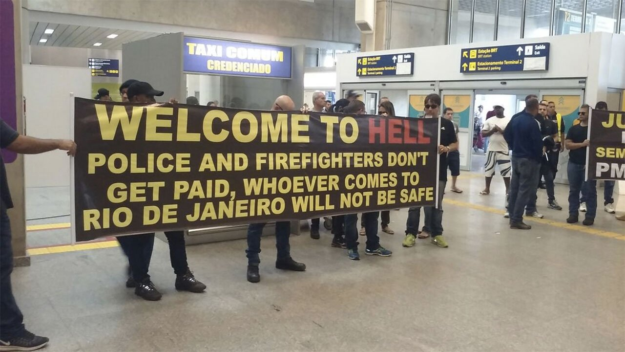 "A ""Welcome to Hell"" sign was held up outside Rio's airport as tourists arrived. Photo: Twitter/Michael Smith"