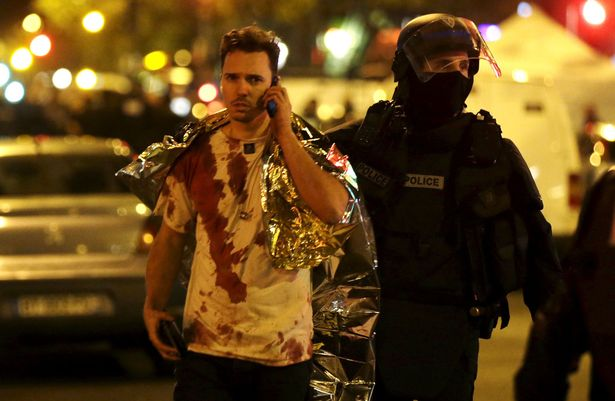 A policeman assists a blood-covered victim near the Bataclan concert hall in Paris