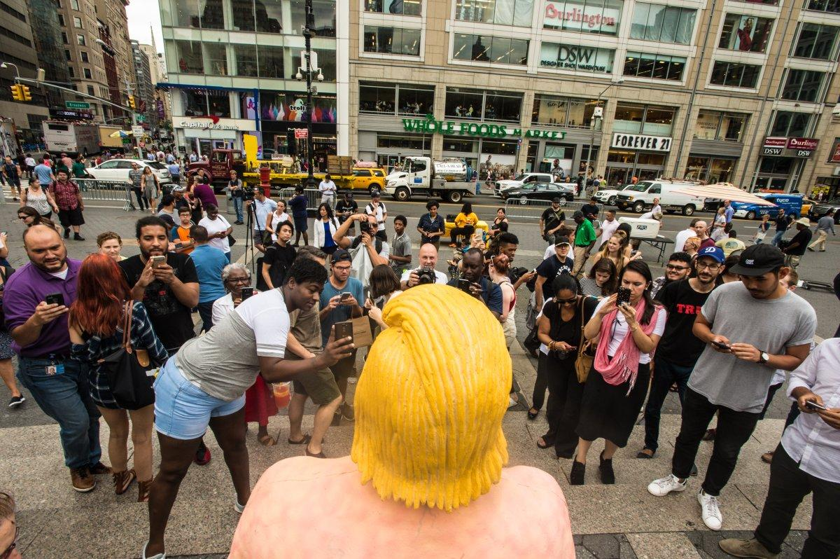 City workers arrived shortly after 1 p.m. to cart naked Trump away.