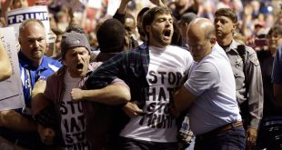 A protester is wrestled off the stage after a campaign rally for Donald Trump was canceled
